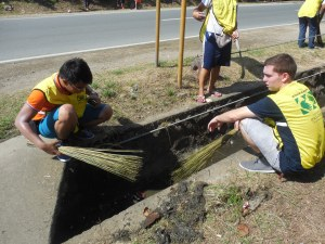 Participating in a service project - cleaning out a gutter!